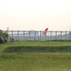 JAL jet taxiing past blast wall