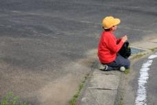 Child playing baseball under a flight path